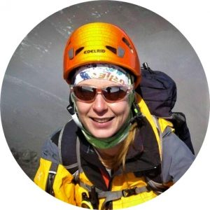Elisabeth Gschösser with a yellow jacket, red sunglasses and orange mountaineer helmet