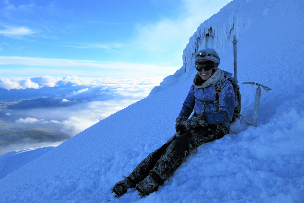 female Mountaineer sitting on the glacier of Cotopaxi